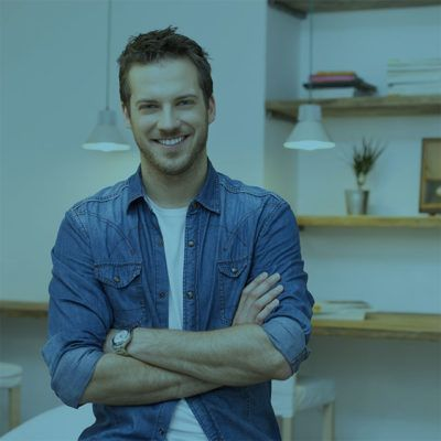 Portrait of smiling young businessman with armcrossed at office